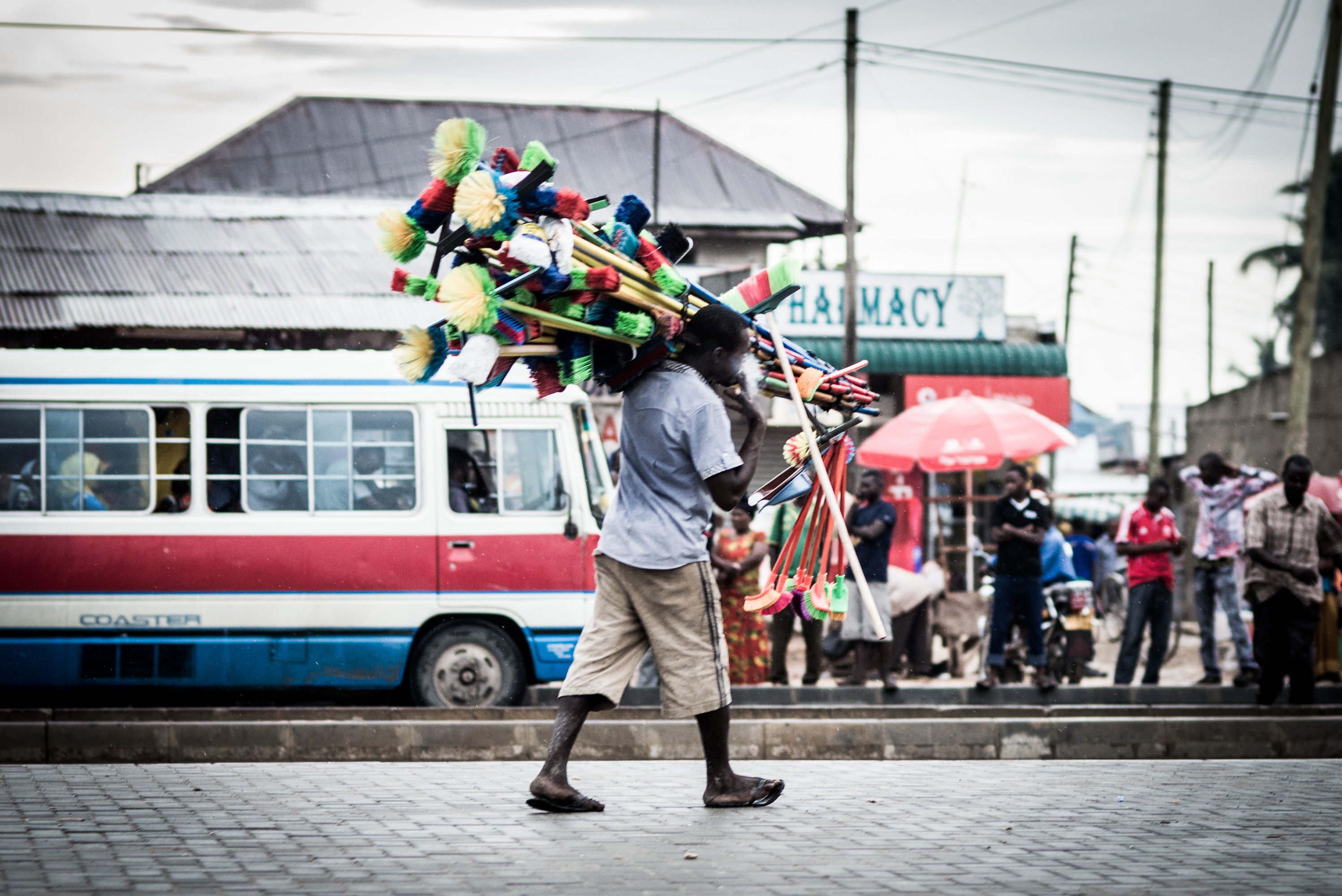 Man carries many brooms over shoulder in street