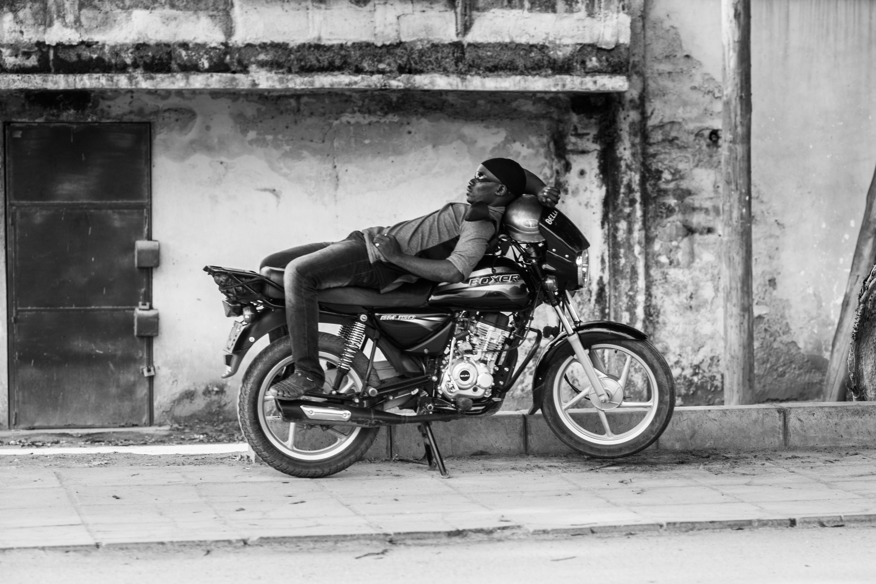 Man asleep on a motorcycle.