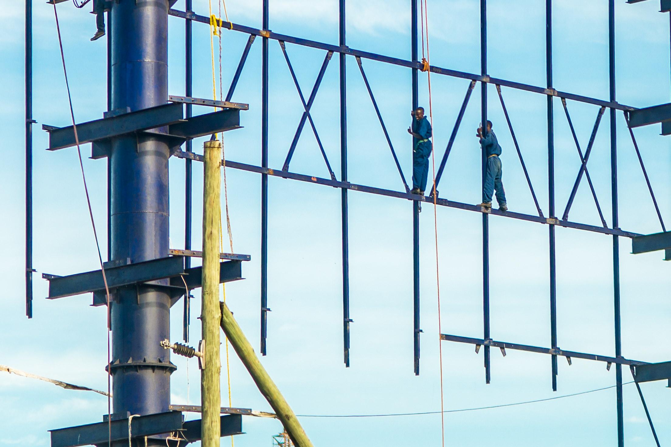 Men working up high on a bilboard
