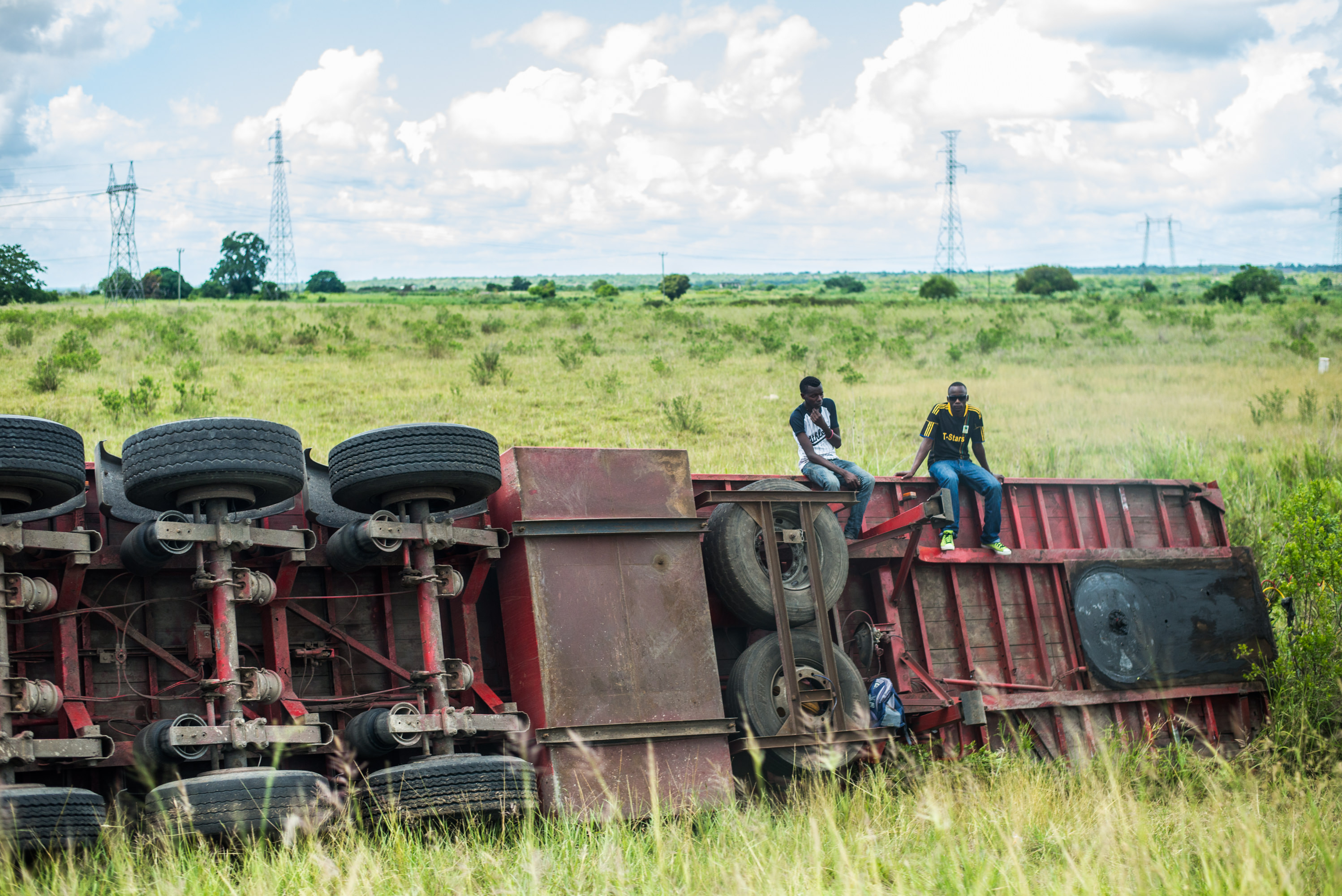 Two men sit on overturned truck by the side of the road in Tanzania.