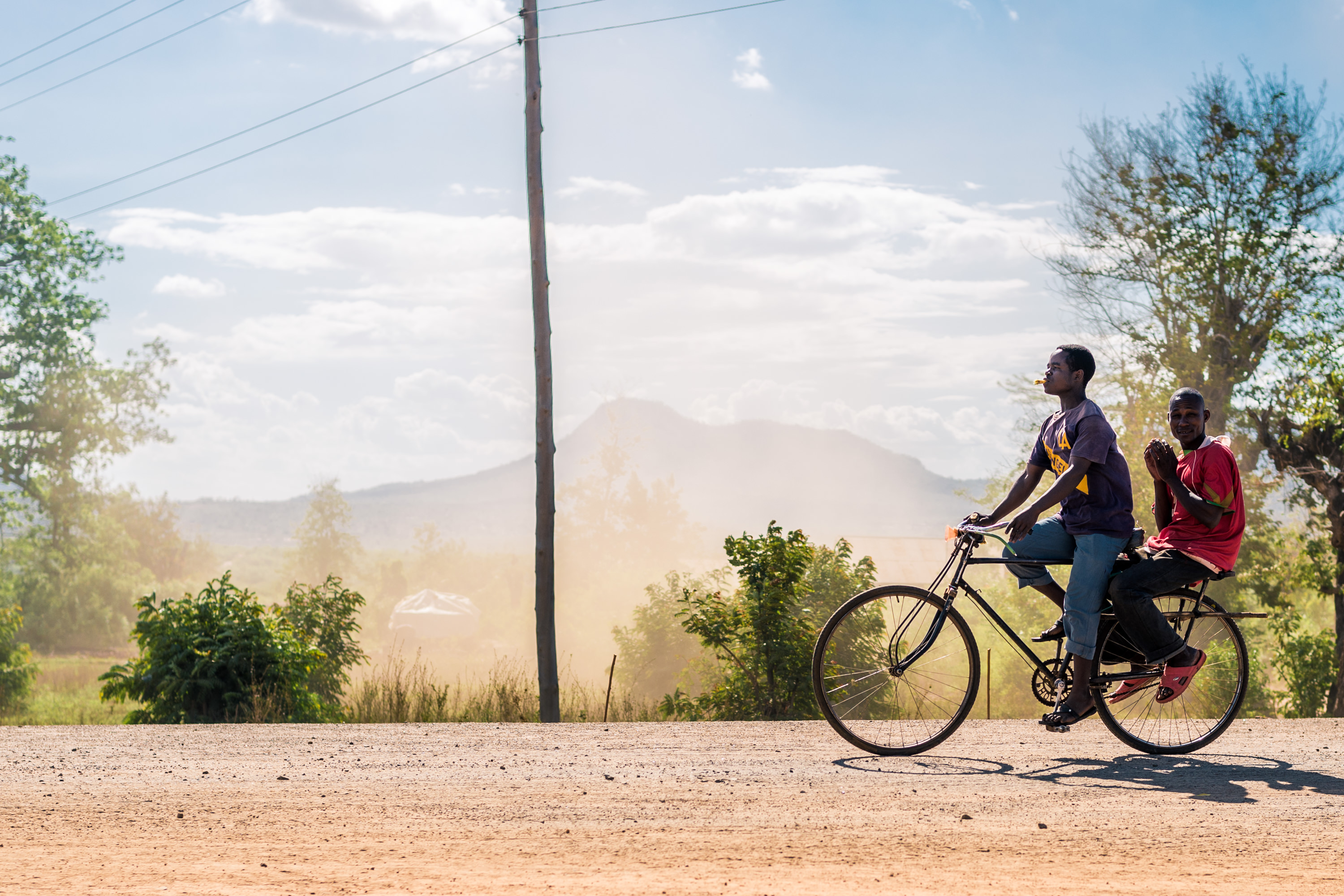 Two men ride tandem on a bicycle on a dirt road in Tanzania