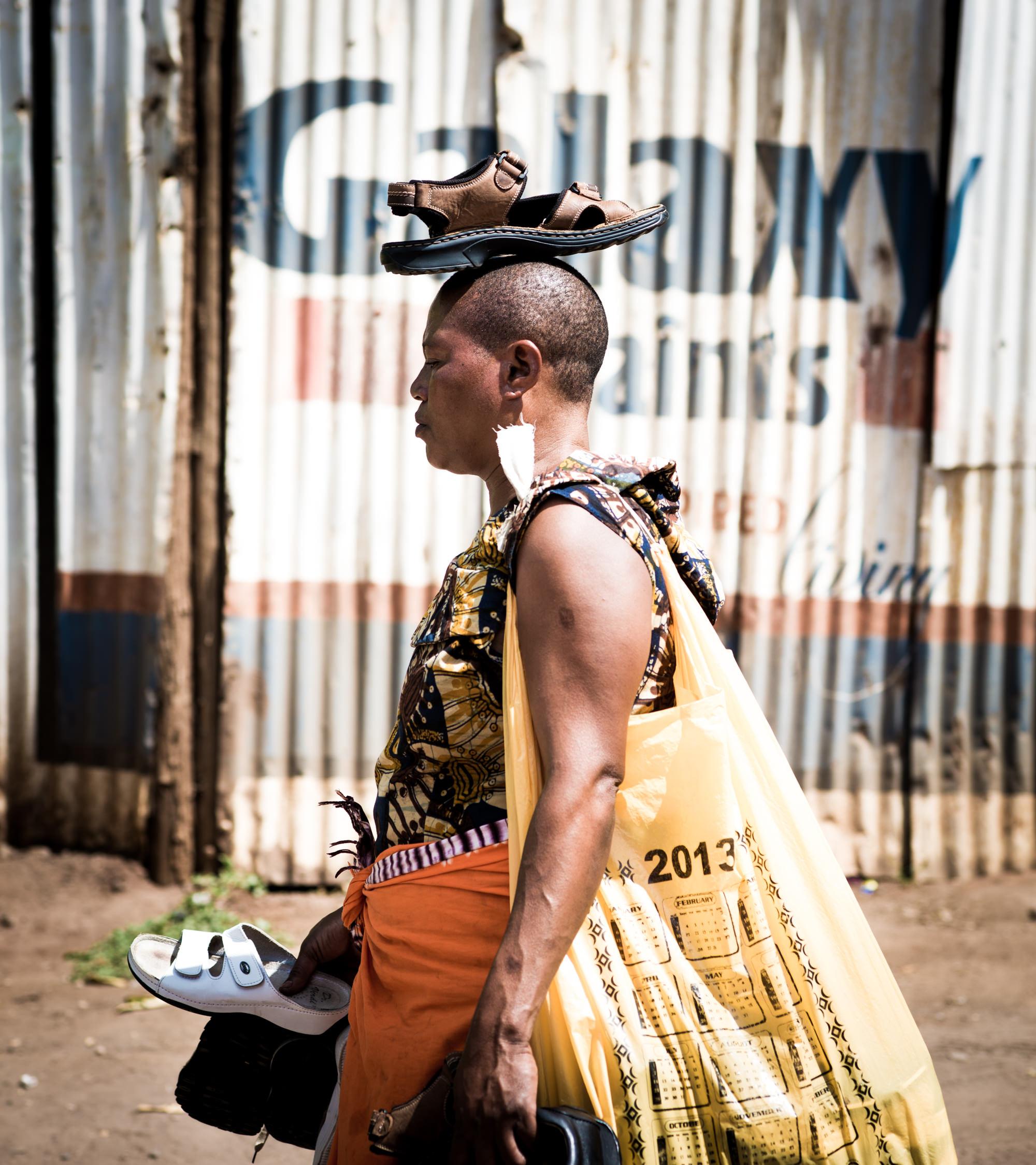 Woman balancing a shoe on her head in Tanzania