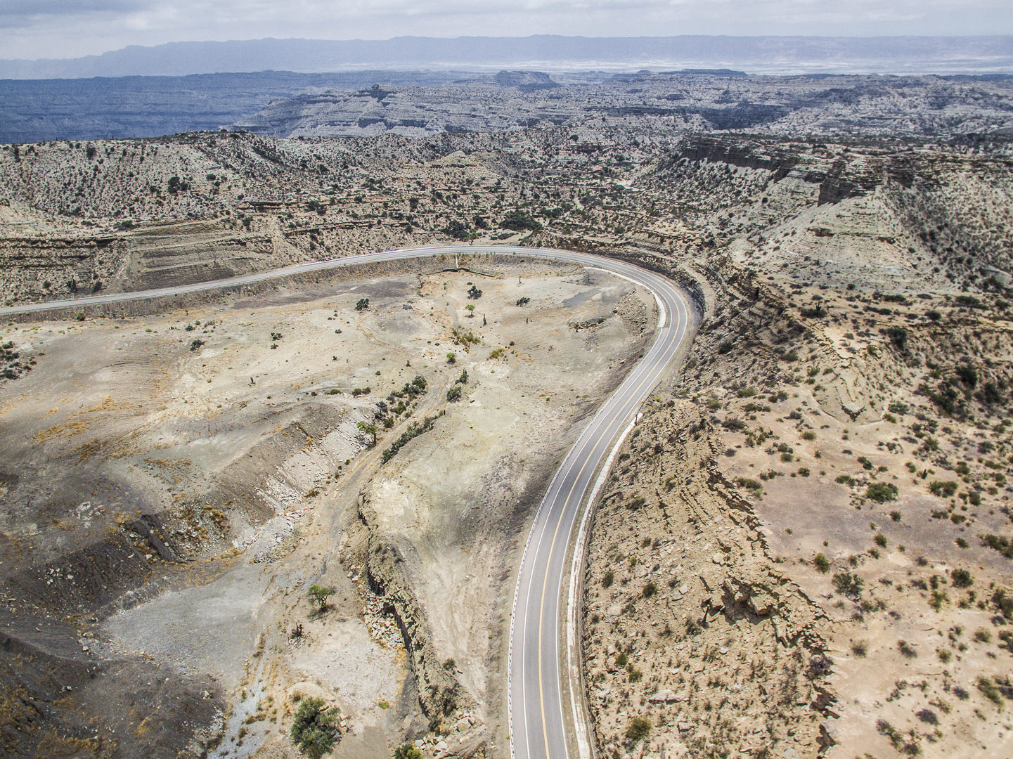 Aerial photography of road surrounded by arid land and mountains